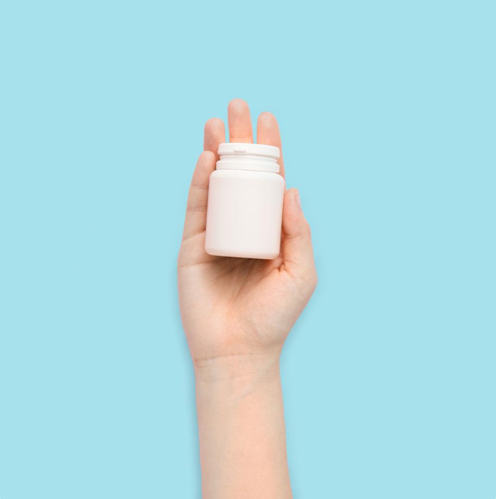 hand holding a plastic prescription bottle